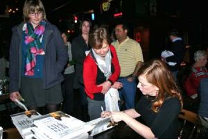 Susan Orleans signs books at her 2012 University of Michigan Club Portland event at the Thirsty Lion Pub.
